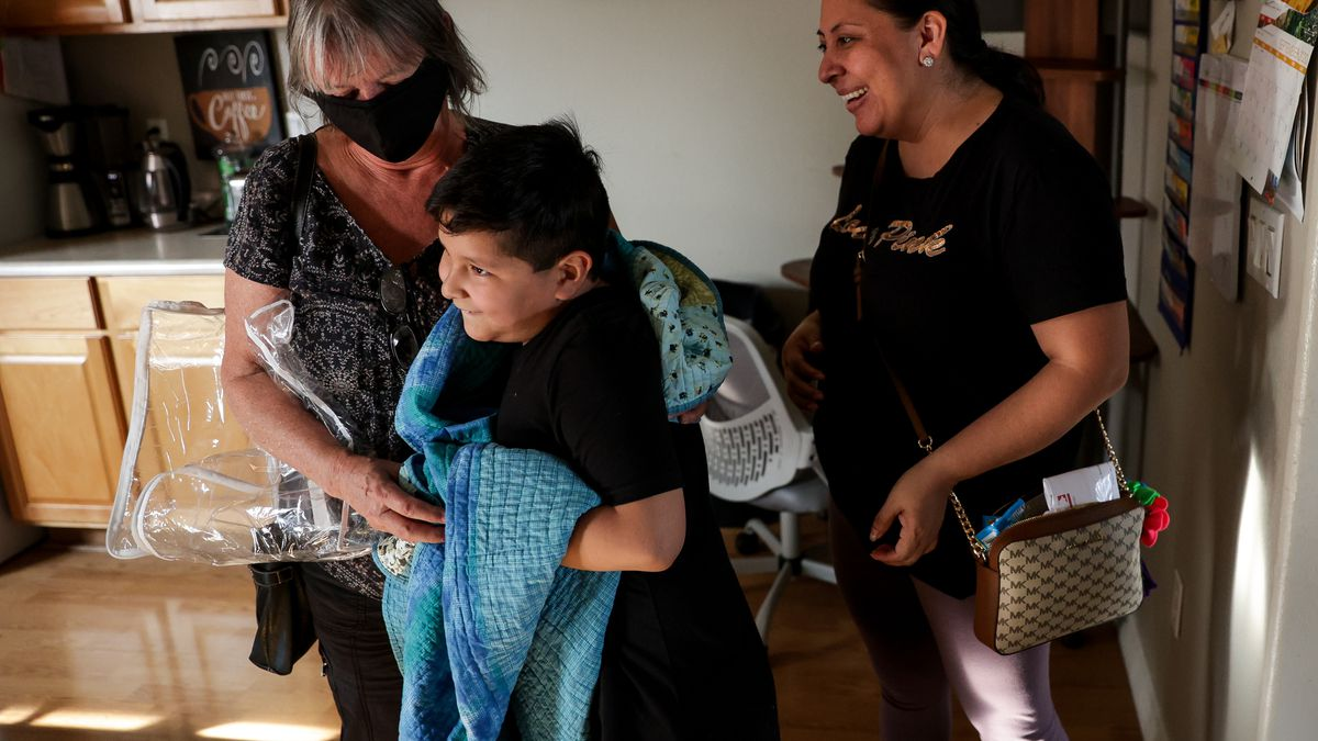 Laura Avalos, right, watches as her son, Christopher Chavez, 7, hugs Peggy Harper after she gave him a quilt that she made for him at a friend's home in Medford, Ore., on Wednesday, Sept. 23, 2020. Avalos and her family lost their home in Phoenix in the Almeda Fire and have received help finding housing and with other needs from a network of women aiming to assist migrant and Latino families who were impacted by the fire.