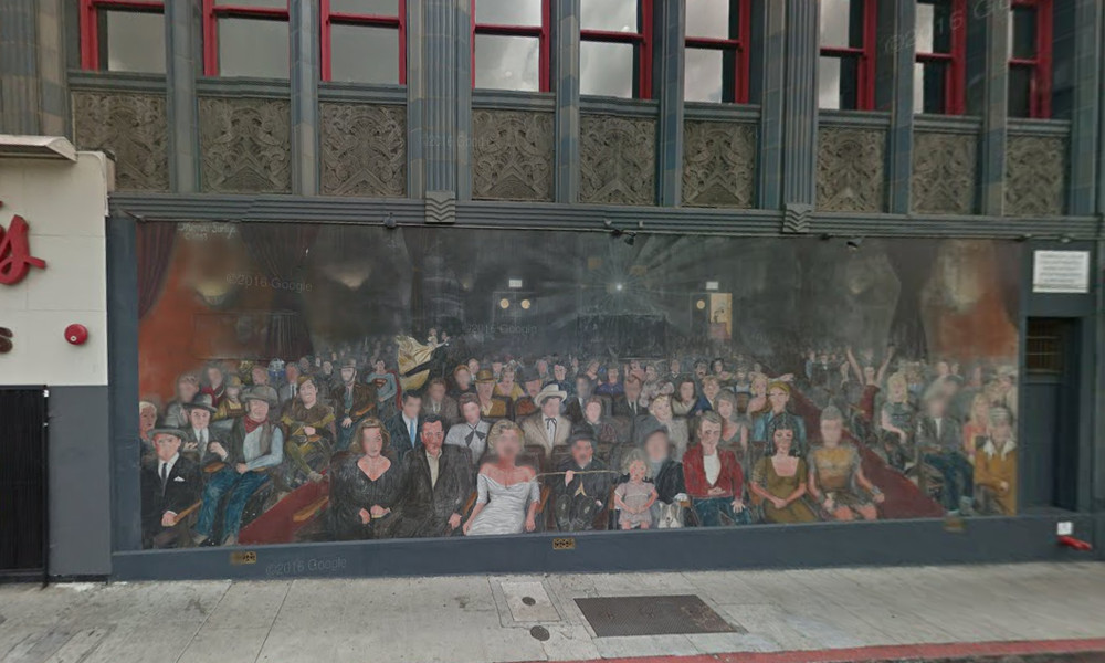 A building with a mural on the side of it. The mural depicts many people sitting in a movie theater.