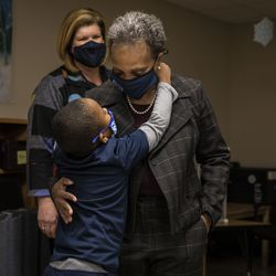 Educators look on as a preschool student approaches Mayor Lori Lightfoot for a hug at Dawes Elementary School at 3810 W. 81st Pl. on the Southwest Side, Monday morning.