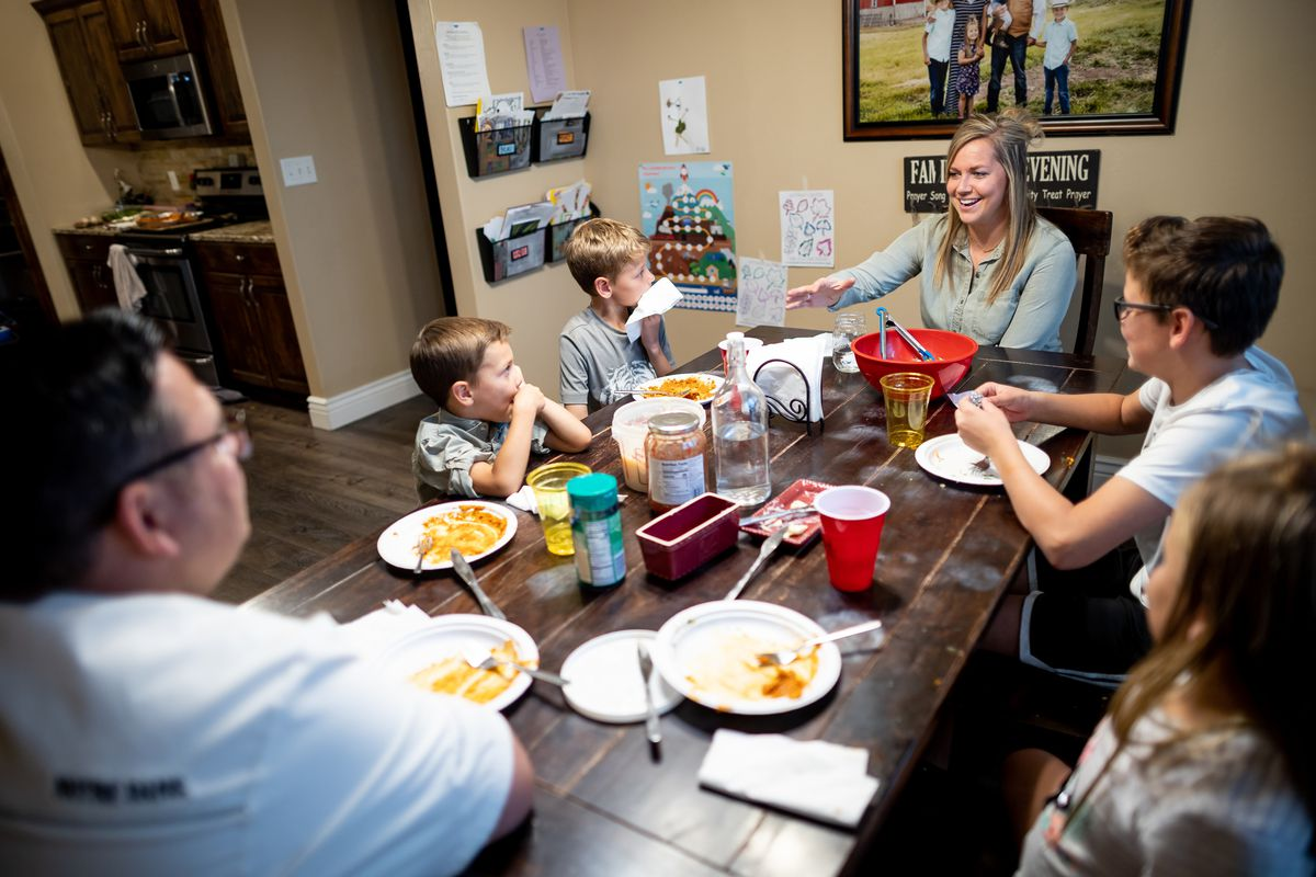 Ashley and Ethan Felix and their children Briggs, 4; Beau, 8; Wyatt, 12; and Andi Lou, 6, left to right, have dinner together at their home in Provo, Utah,  on Tuesday, Oct. 5, 2021. The seventh annual edition of the American Family Survey documents how families made it through the pandemic. The Felix family's challenges included moving so Ethan could go to school full time and challenges getting needed care.