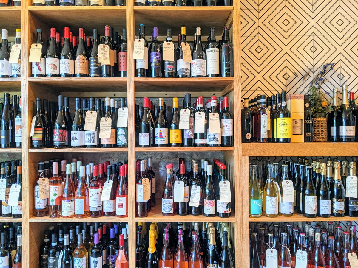 Four rows of wooden shelves are fully stocked with wine bottles.