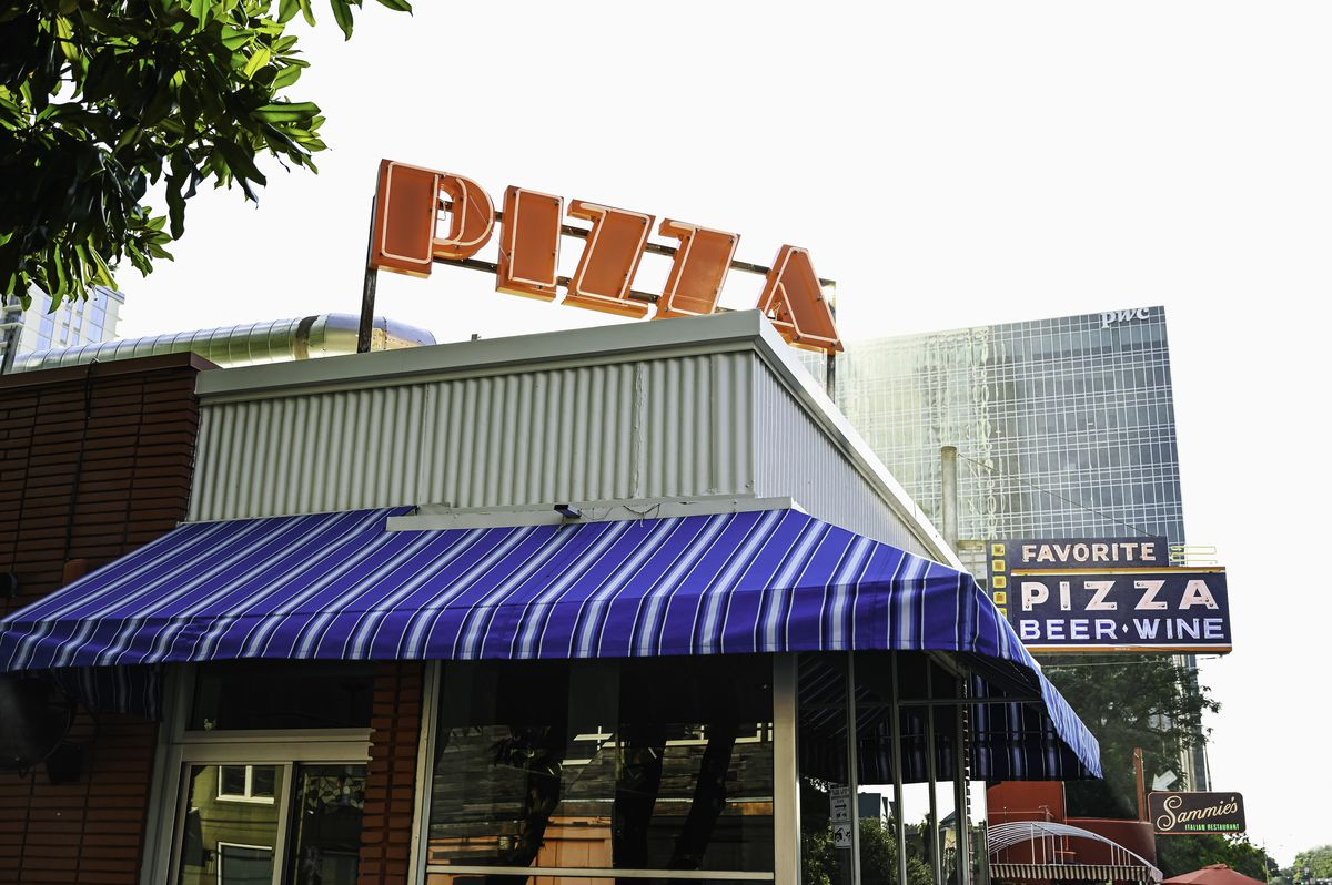 """A corner of a building with a blue-and-white awning with a big sign that says """"Pizza"""""""