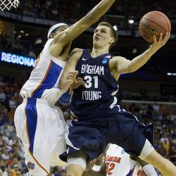 BYU's Kyle Collinsworth puts up a shot as he is guarded by Florida's Alex Tyus as the BYU Cougars take on the University of Florida in at the New Orleans Arena on Thursday, March 24, 2011 in the Sweet 16 round of the NCAA tournament.