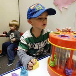Ty, front, and Zander participate in therapy work sessions during the Autism Bridges program at Kids on the Move in Orem, Tuesday, Oct. 15, 2013.