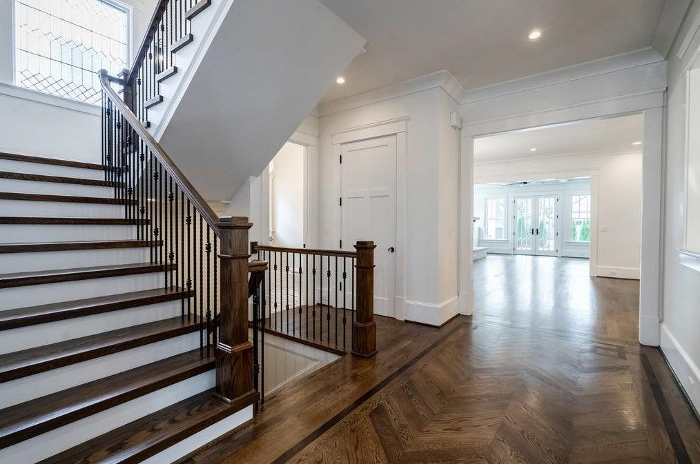 A white hall space with inlaid hardwood floors.