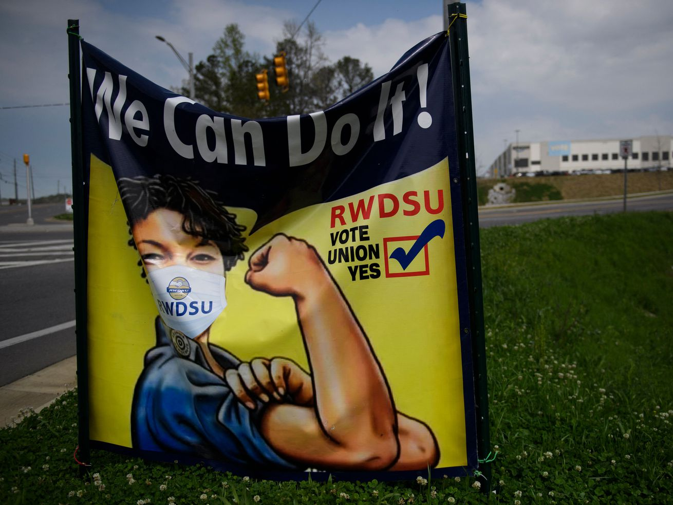 """A pro-union RWDSU sign beside a road has a picture of a worker curling their arm in a pose reminiscent of Rosie the Riveter and the words """"We can do it!"""""""