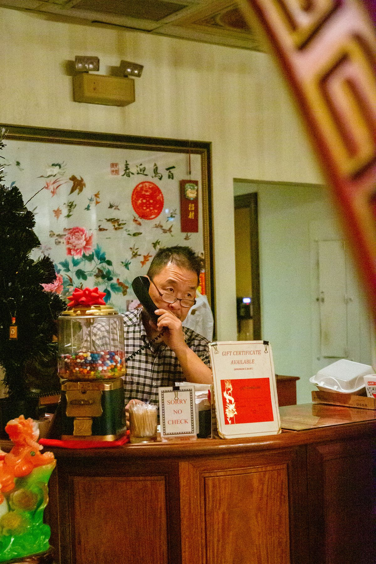 Man on phone sitting behind a counter.