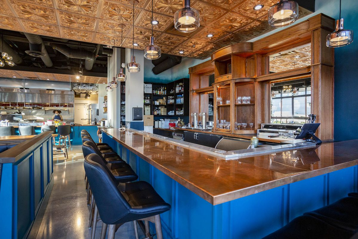 The blue painted and wood-topped bar at Communion with a copper-toned roof and the kitchen seen in the back