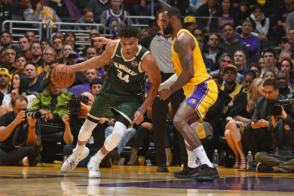Giannis Antetokounmpo of the Milwaukee Bucks handles the ball while LeBron James of the Los Angeles Lakers plays defense on March 6, 2020 at STAPLES Center in Los Angeles, California.