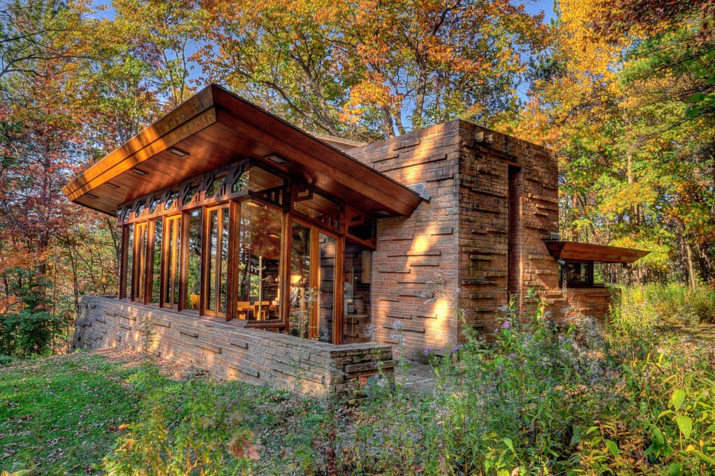 The Seth Peterson Cottage by Frank Lloyd Wright. The facade is red brick with wood framing. There are tall windows on the front of the house. The house is surrounded by trees with multicolor leaves.