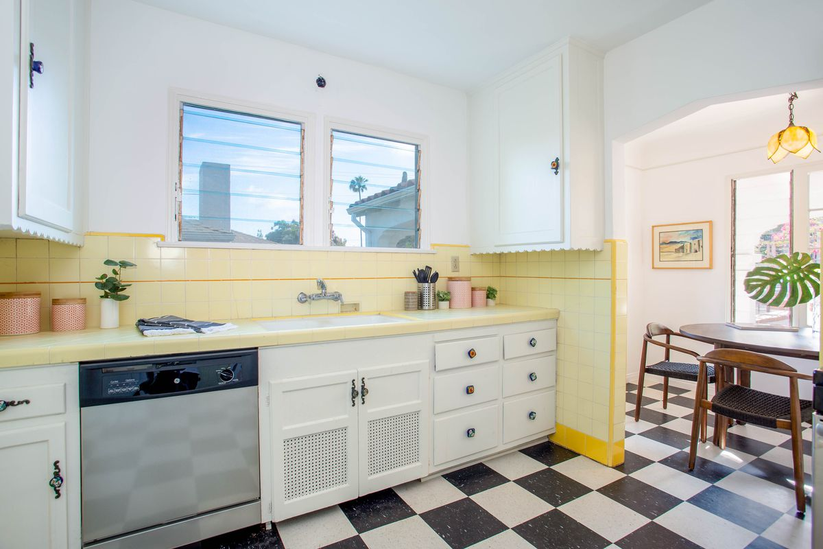 Kitchen features original yellow tiles and scalloped-edge cabinetry.