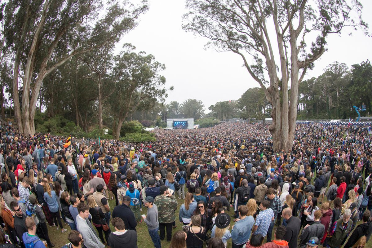A crowd of thousands in Golden Gate Park, with the Outside Lands stage far in the distance.