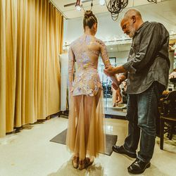 NYCB costume director Marc Happel fixes a loose sleeve.