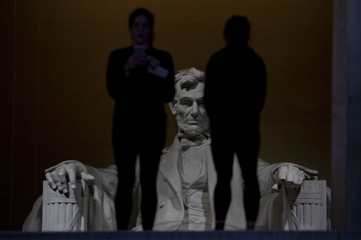 The statue of former President Lincoln looms in the distance as tourists visit the Lincoln Memorial on December 22, 2018, in Washington, DC.