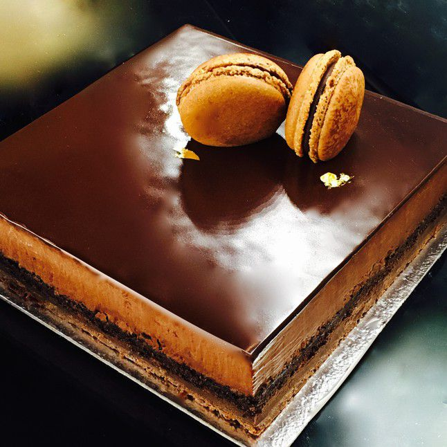 Layers of chocolate topped with two macarons