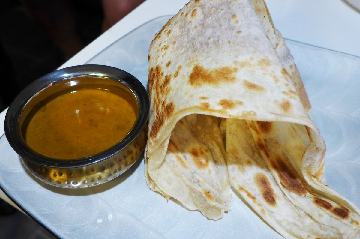 A flaky flatbread casually rolled on a plate with a bowl of curry dip beside it...