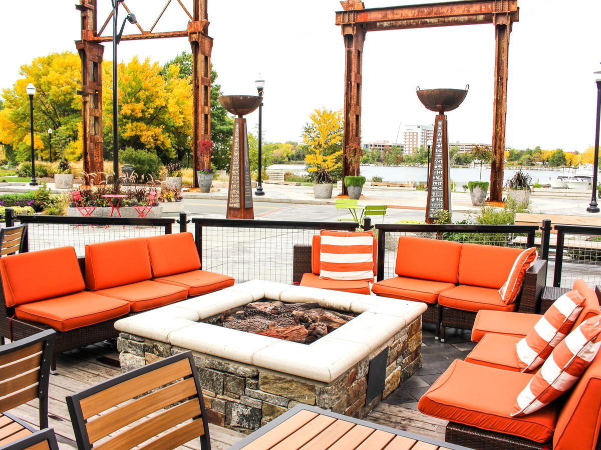 Orange outdoor lounge seating is set up around a fire pit. There's a river visible in the background.