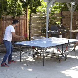 The designer's husband (right) and friend engaged in a friendly game of ping pong just off the studio's patio, the perfect hangout space.