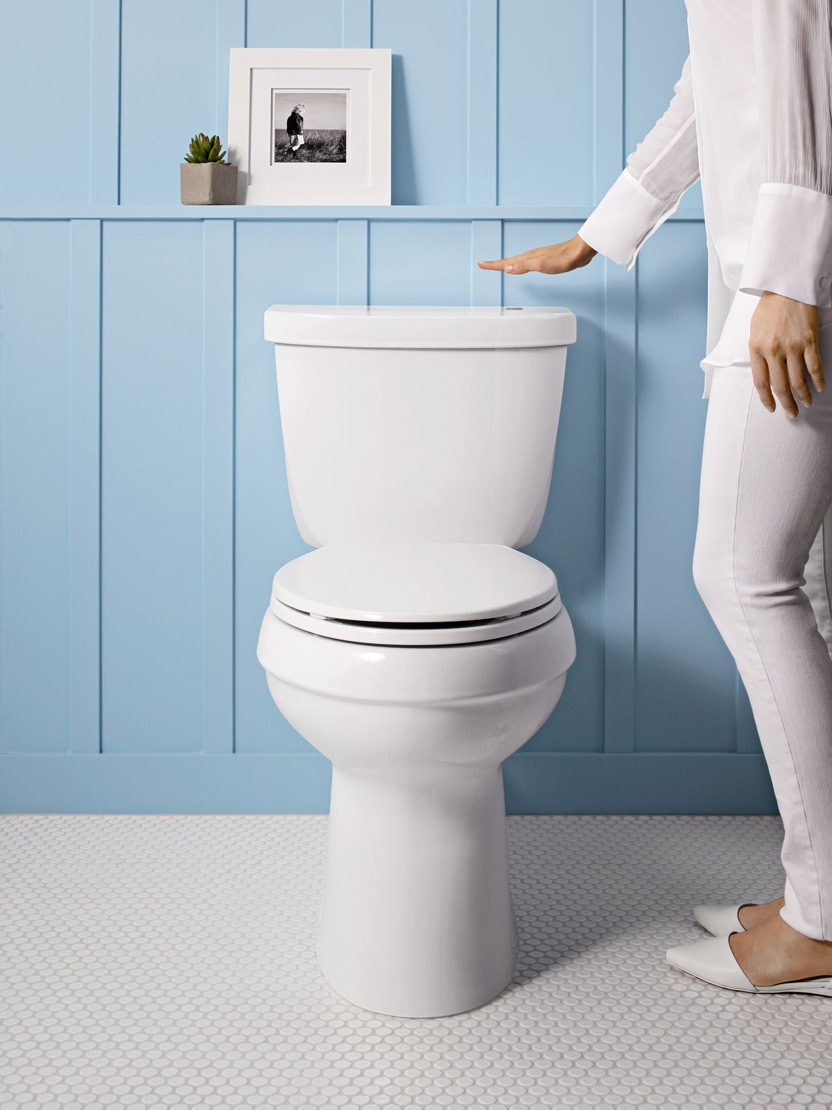 Woman holding hand over the hands-free flush feature on toilet.