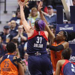 Washington Mystics' Stefanie Dolson (31) puts a shot up over the outstretched arm of Connecticut Sun's Kelsey Bone (3).