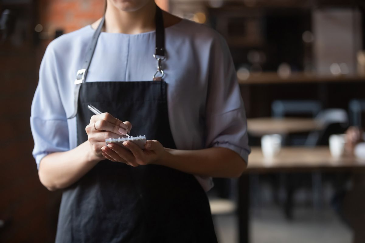 A server is ready to take an order, holding a notepad.