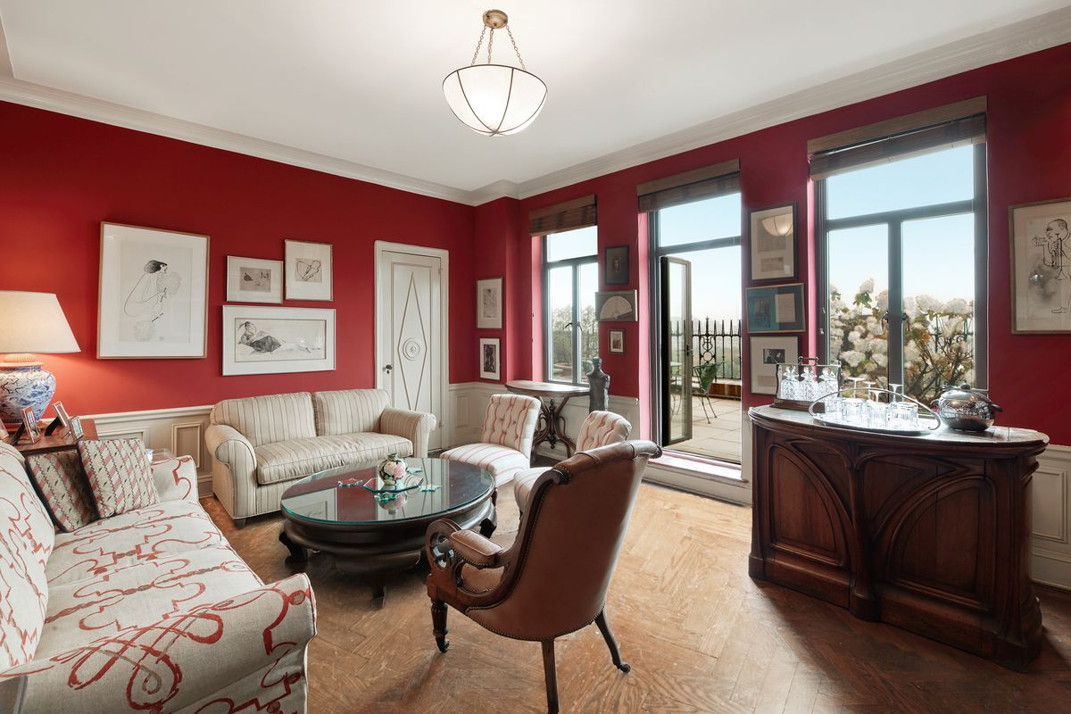 A room with red walls and a door to a large terrace.