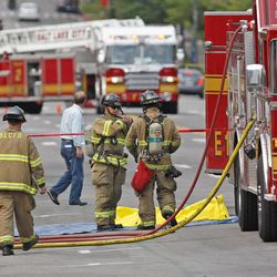 Fireman stand near a manhole cover (covered by a plastic tarp) that was blown off near the corner of 300 South and 200 East Monday, Aug. 13, 2012, in Salt Lake City.