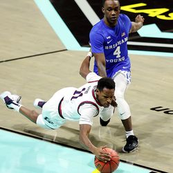 Gonzaga Bulldogs guard Joel Ayayi (11) dives around Brigham Young Cougars guard Brandon Averette (4) trying to get the loose ball as BYU and Gonzaga play in the finals of the West Coast Conference tournament at the Orleans Arena in Las Vegas on Tuesday, March 9, 2021. Gonzaga won 88-78.
