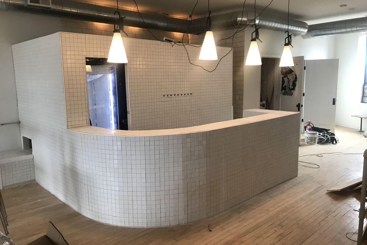 A new curved tile bar with pendant lights takes shape in the Collect space.