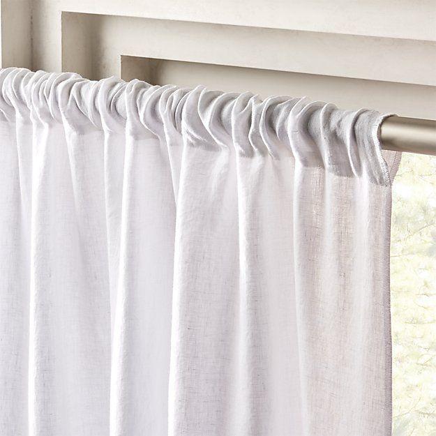 Closeup of white curtain hanging on metal rod.