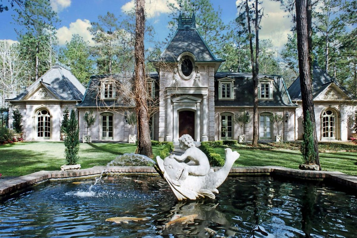 Shot of front of an opulent French-style chateau with brick facade and French doors and a large fountain in front of with a statue of a cherub on top of a fish.