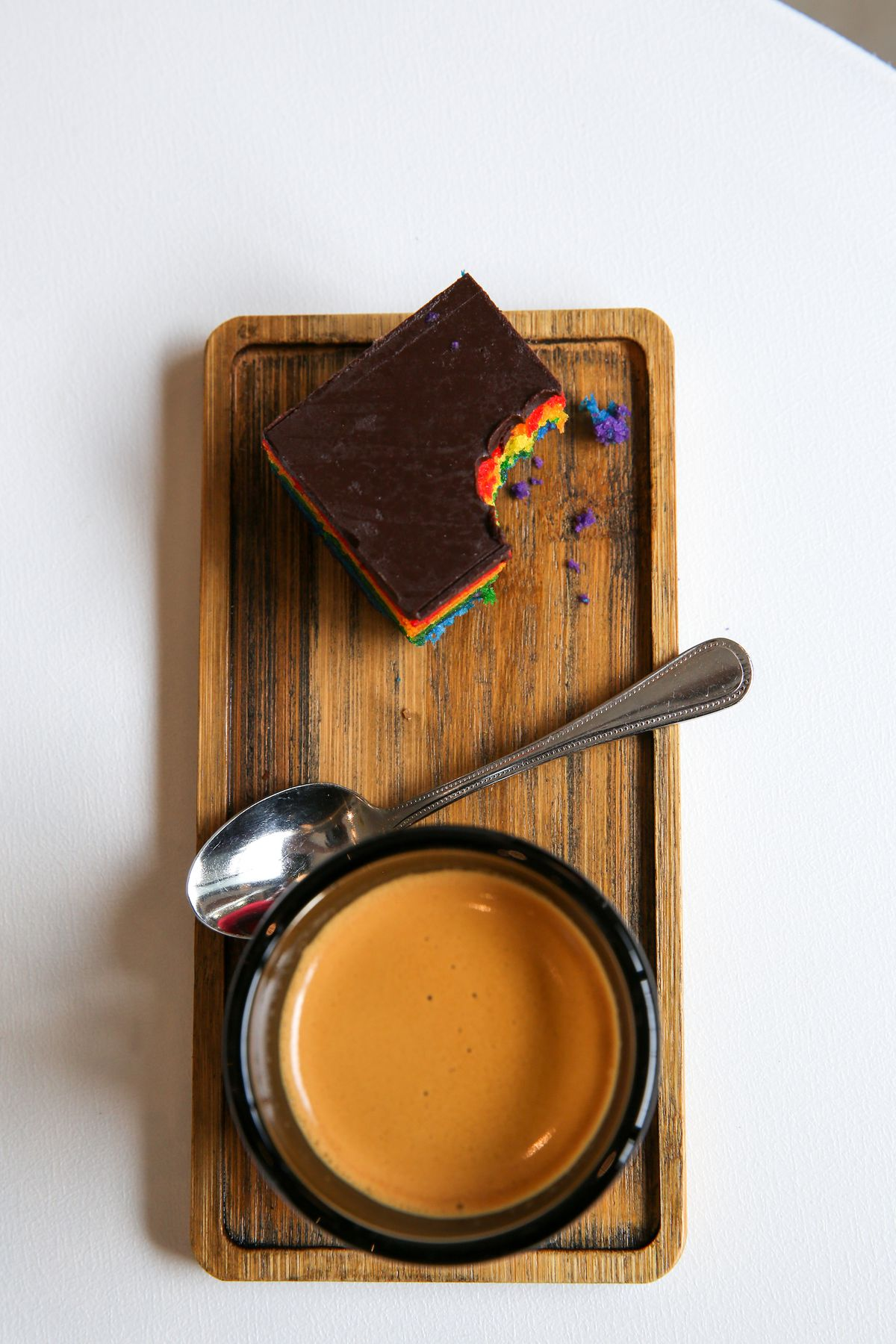 A wooden board that holds a cup up piece of rainbow cake, a silver spoon, a small mug with an espresso.