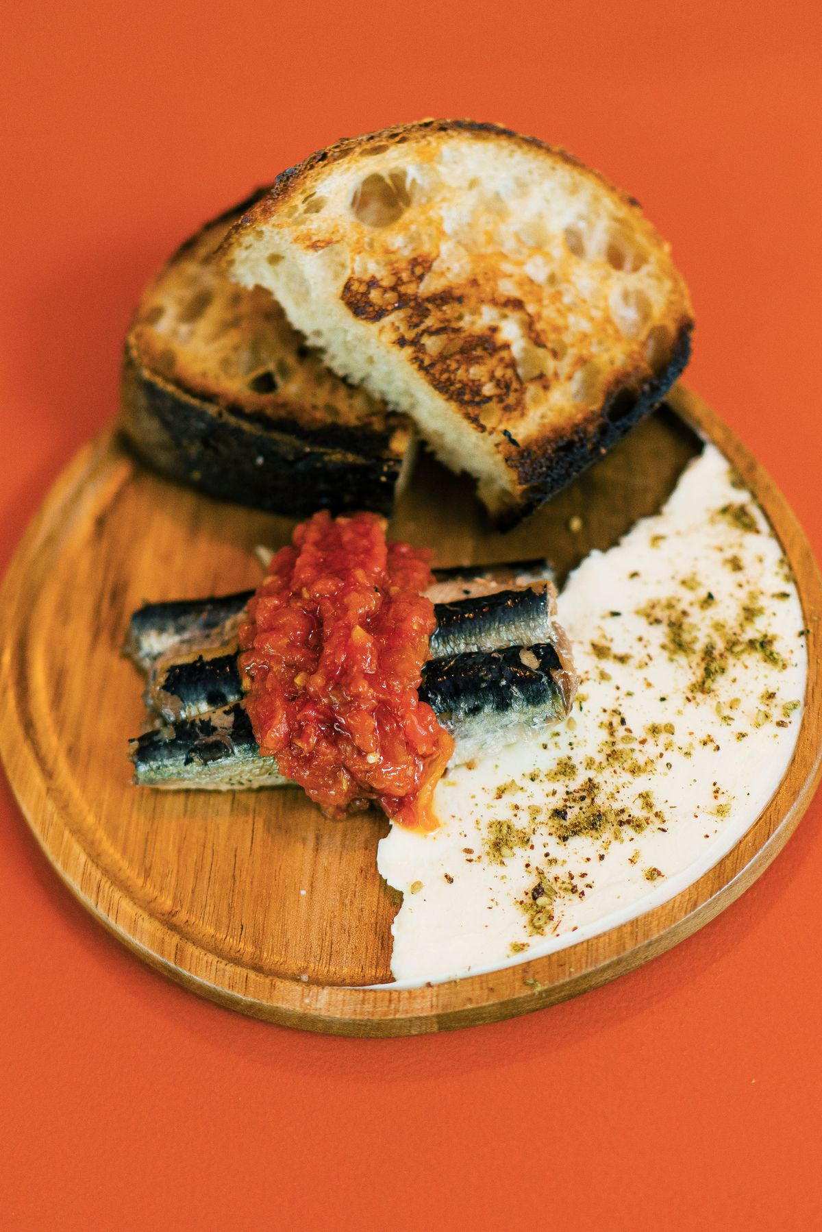 anchovies on a wooden plate with bread on a red background