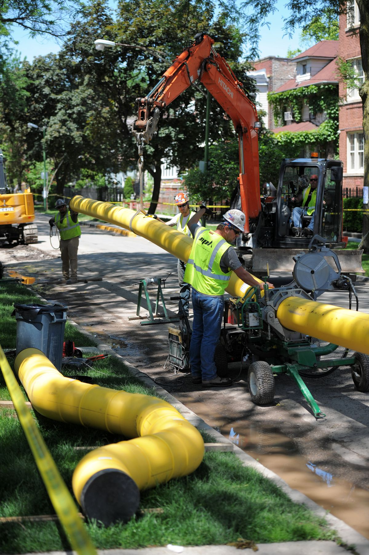 Workers stand over new gas pipelines to be installed on an Albany Park street in a photo taken last summer. Spending for the project has ballooned over the years and could ultimately cost $8 billion to $11 billion.