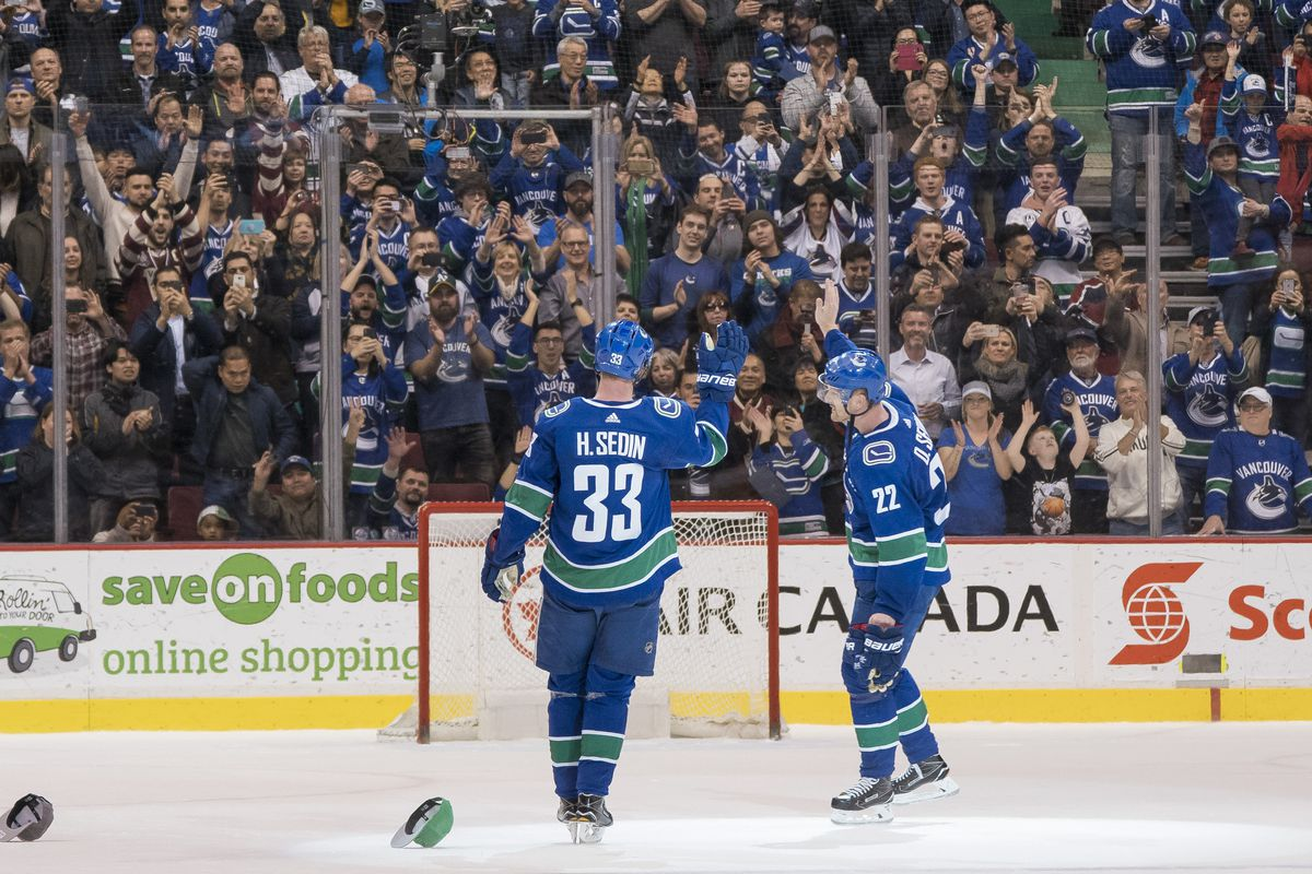 VANCOUVER, BC - OCTOBER 5: Daniel Sedin #22 and Henrik Sedin #33 of the Vancouver Canucks salute the fans after playing in their final home game of their career against the Arizona Coyotes in NHL action on April, 5, 2018 at Rogers Arena in Vancouver, Brit