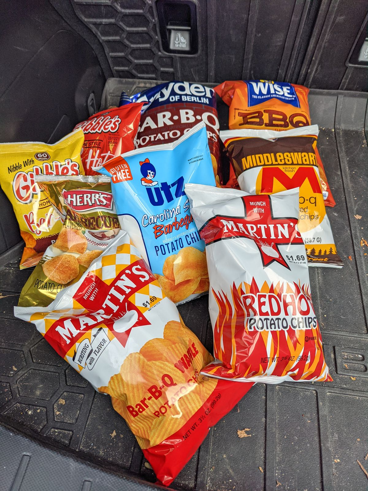 Nine different bags of potato chips, including varieties from Herr and Utz, in the trunk of a car.