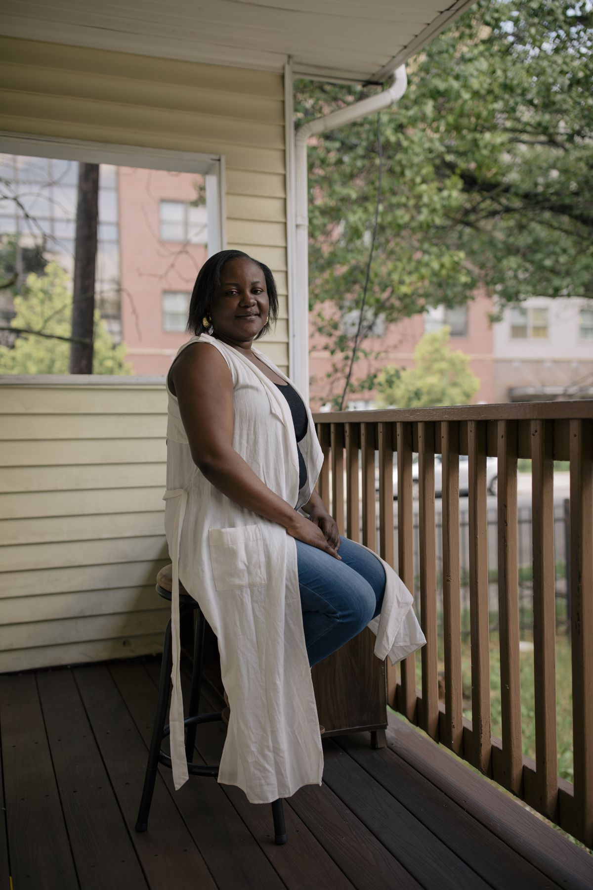 A portrait of Oyefunmilola Dairo on her wooden front porch on a bright day. She is seated on a stool wearing a large flowing white blouse as buildings and trees are reflected in a window just behind her.