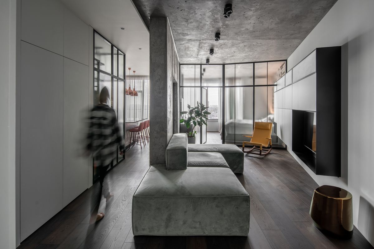 Woman walking through apartment with concrete walls, gray furniture, and glass.