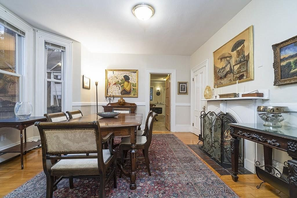 A dining room with a long table and chairs next to a fireplace.