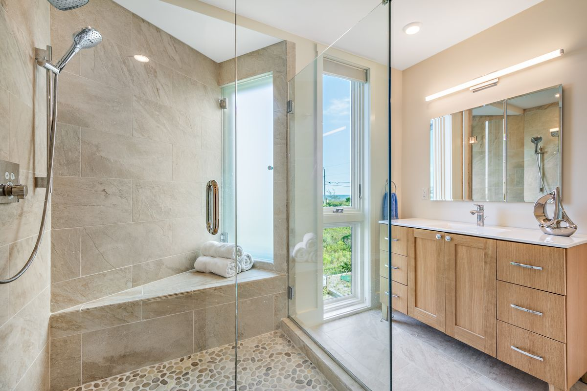 A bathroom has a glass shower, windows, and a single sink with wood cabinets below.