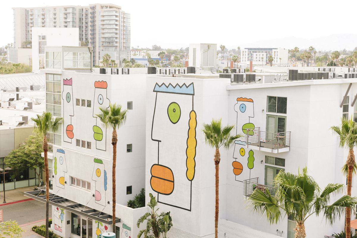 White apartment buildings with very colorful abstract faces painted on the side of the building. Palm trees in front, city buildings behind.