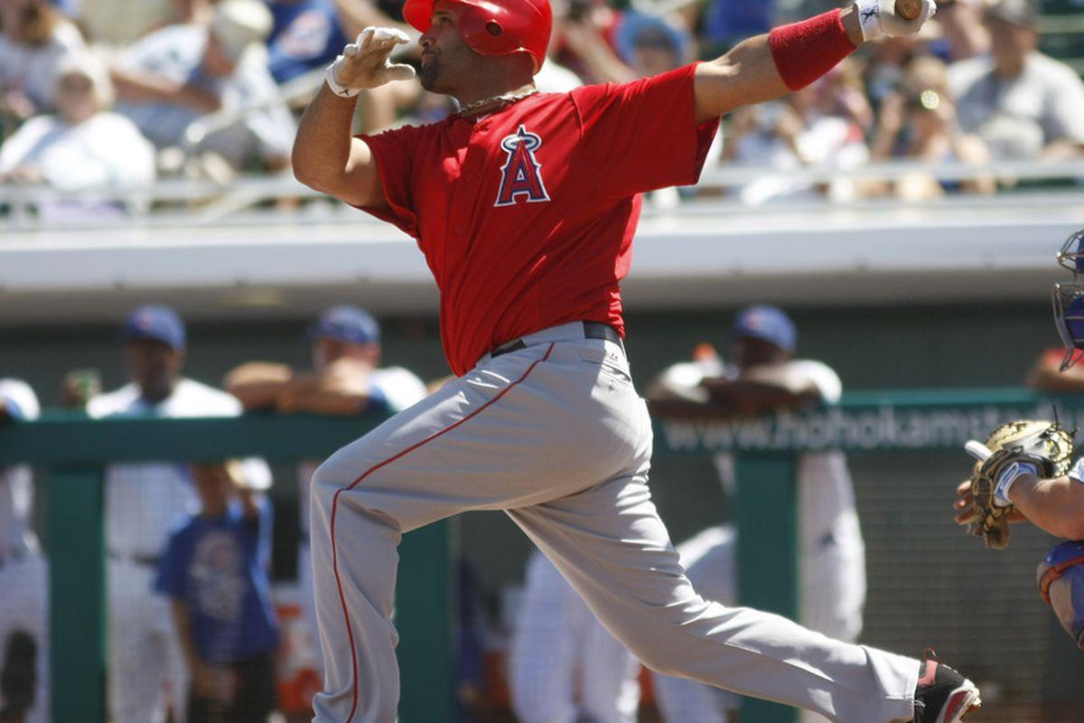 March 31, 2012; Mesa, AZ, USA; Los Angeles Angels first baseman Albert Pujols (5) hits a two run homerun against the Chicago Cubs in the first inning at HoHoKam Stadium.  Mandatory Credit: Rick Scuteri-US PRESSWIRE