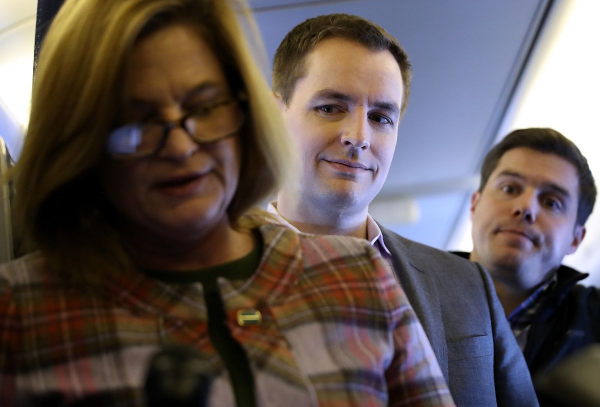 IN FLIGHT, UNITED STATES - OCTOBER 28: Robby Mook, campaign manager for Democratic presidential nominee former Secretary of State Hillary Clinton looks on as Jennifer Palmieri, communications director, speaks aboard the campaign plane while traveling to C