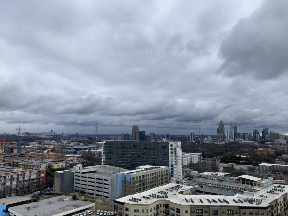 A city skyline under gray skies, with many buildings of various colors.