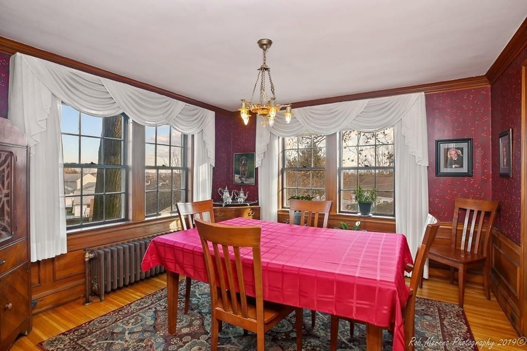 A corner dining room with a table and chairs and two windows.
