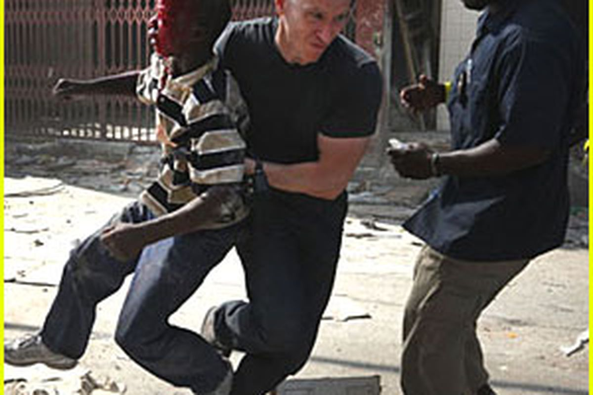 Kevin Acee rescues an injured boy during riots in Haiti