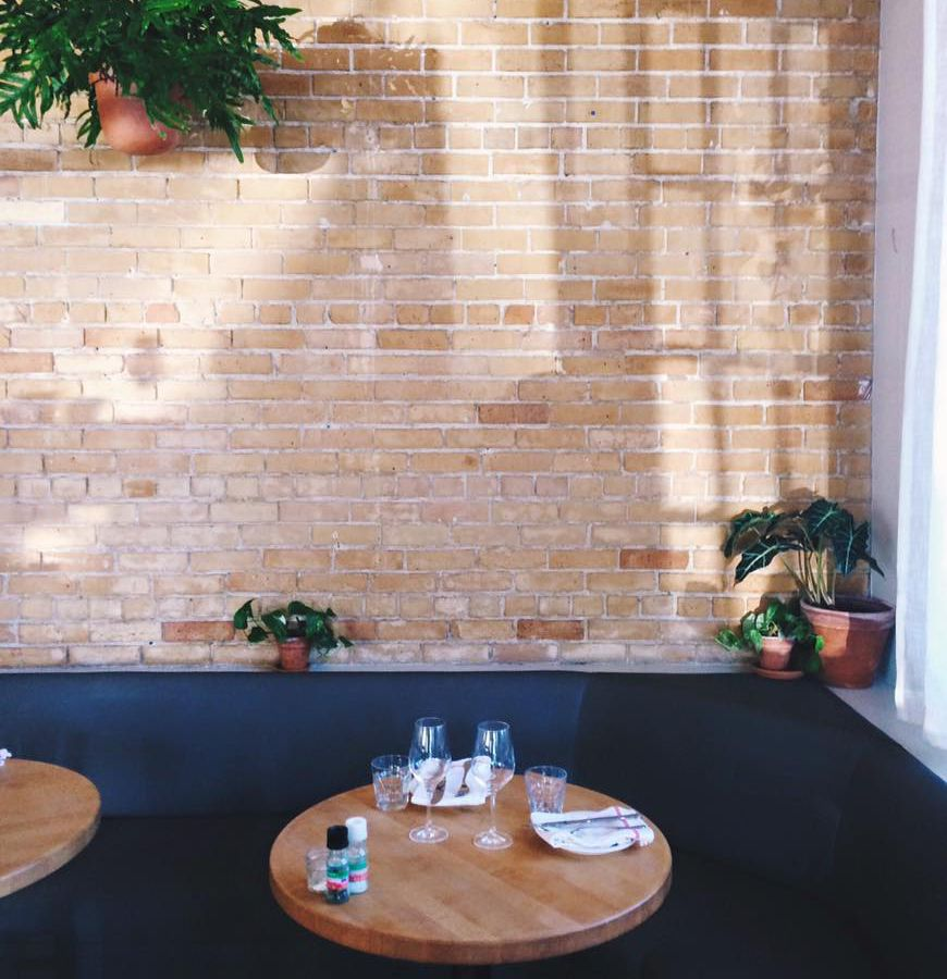 A circular wooden table set with wine glasses, napkins, and plates, in front of a blue banquet agaist a brick wall with green plants
