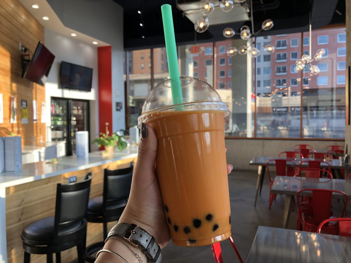 Image of Wild Poké Thai tea with classic black tapioca pearls in center. The background features the restaurant's interior, with a bar on the left, large windows in the background, and low tables and red chairs on the right.