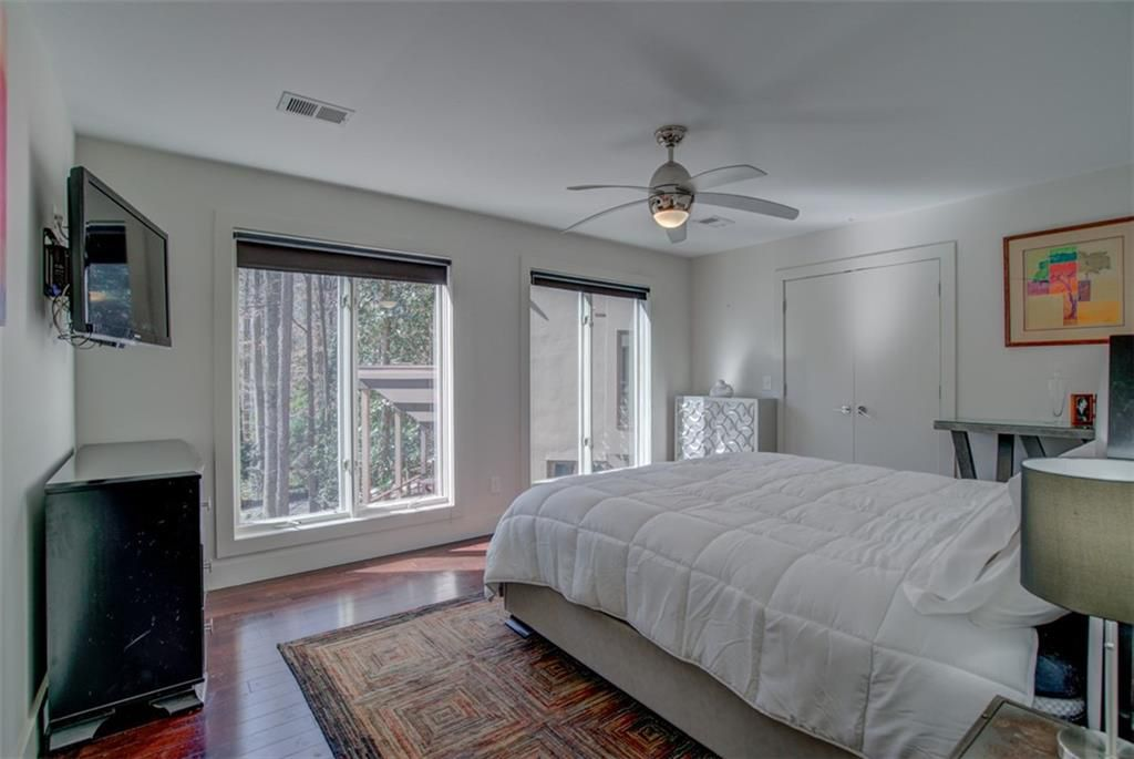 A white master bedroom with big windows and woods outside.