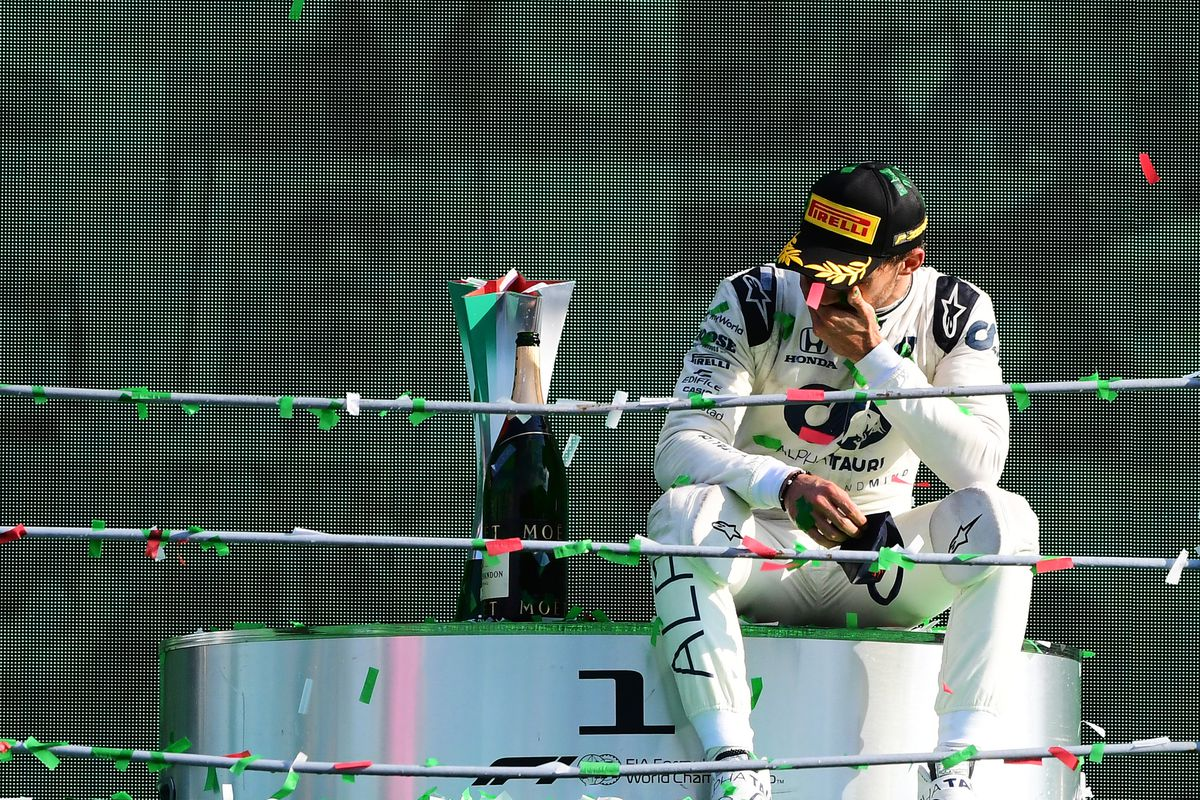 Race car driver Pierre Gasly sits on the winner's dais beside a bottle of champagne after the F1 Grand Prix.